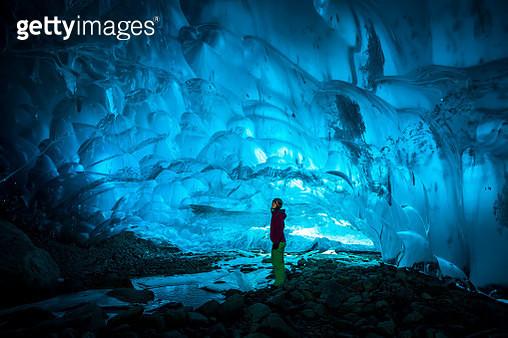 Woman exploring glacial ice cave. - gettyimageskorea
