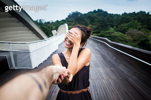 Smiling young woman standing on a bridge, covering her face, holding man's hand. - gettyimageskorea