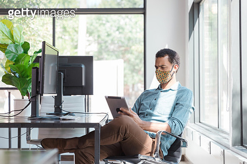 Mid adult man with face mask brainstorms ideas on tablet - gettyimageskorea