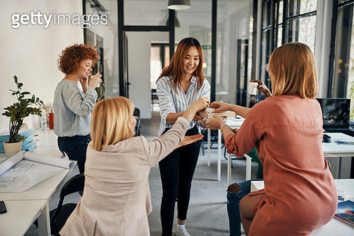 Businesswoman serving coffee to colleagues in office - gettyimageskorea