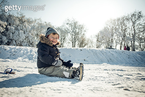 Cute happy boy enjoying on snow at the park and looking at camera. Copy space. - gettyimageskorea