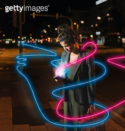 Young woman looking at cell phone by night, composite - gettyimageskorea
