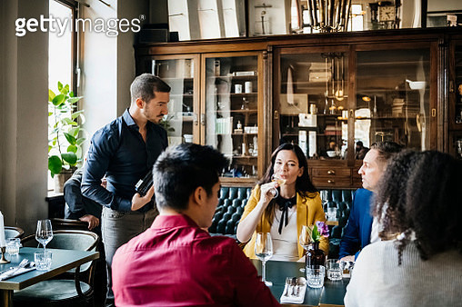 Waiter Serving Wine To Table Of Customers In Restaurant - gettyimageskorea