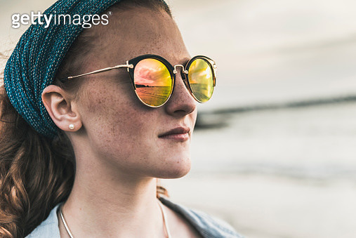 Reflection of clouds in sunglasses of young woman at sunset on the beach - gettyimageskorea