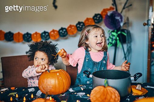 Two children at a table with a pumpkin taking out the middle and laughing. - gettyimageskorea