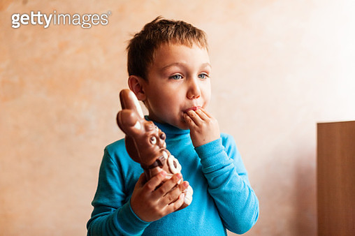 Toddler boy eating chocolate bunny - gettyimageskorea