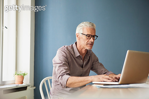 Mature man using laptop on table at home - gettyimageskorea