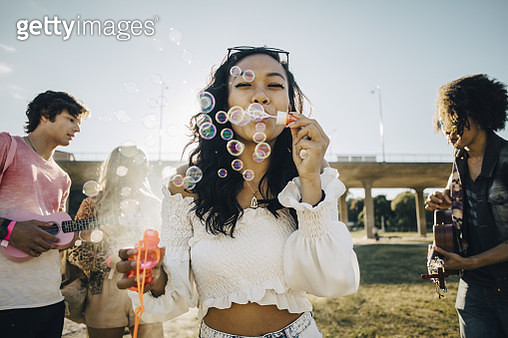 Woman blowing soap bubbles while friends playing ukulele during music event - gettyimageskorea