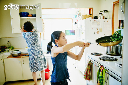 Young girl flipping green beans in pan on stove - gettyimageskorea