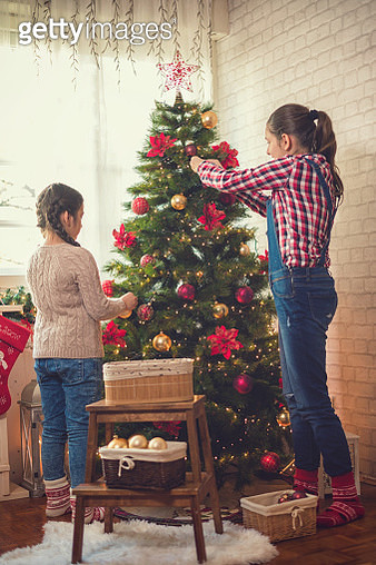 Family decorating the Christmas tree at home - gettyimageskorea