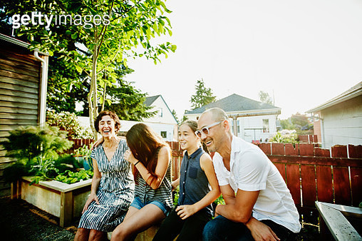 Laughing family sitting together in backyard garden of home on summer evening - gettyimageskorea