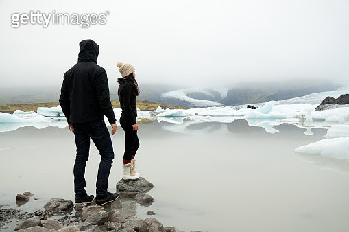 Man and woman stand on edge of glacier lake - gettyimageskorea