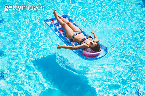 Girl relaxing  and sunbathing on inflatable mattress in a swimming pool - gettyimageskorea