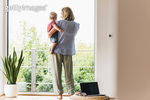 Mother carrying son, looking out of window - gettyimageskorea