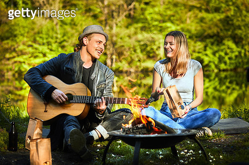 Happy young couple sitting at the fire playing guitar - gettyimageskorea