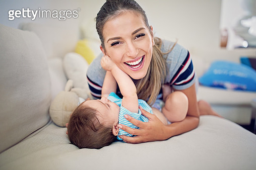 Portrait of mother playing with her little baby on the sofa - gettyimageskorea