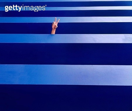 Cropped Hand Showing Peace Sign On Blue Wall - gettyimageskorea
