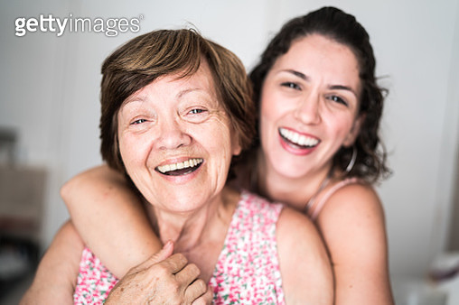 Happy adult mother and daughter embracing - gettyimageskorea