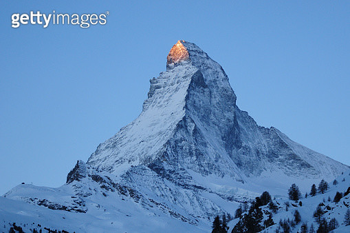 The peak of the Matterhorn (Cervino) mountain in the Alps spotlit by the first rays of the rising sun, seen from Zermatt in Switzerland - gettyimageskorea
