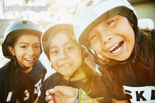 Portrait of smiling young female friends making faces during skateboarding camp - gettyimageskorea