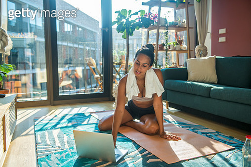 A young sports woman exercising using a laptop - gettyimageskorea