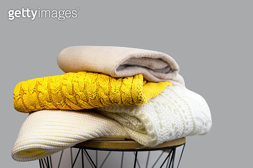 Stack of Trendy Bright illuminating Yellow, Gray and White Woolen Knitted Sweaters. - gettyimageskorea