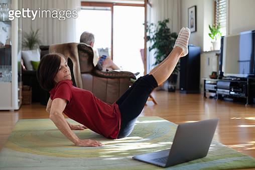 Senior woman exercising at home, using laptop to follow online tutorial - gettyimageskorea