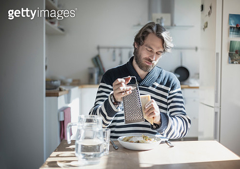 Holding cheese grater over pasta dish - gettyimageskorea