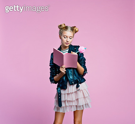 Surprised female teenager wearing black leather jacket and pink tulle skirt holding pink notebook and pen in hands. Cute girl writing a diary. Studio shot on pink background. - gettyimageskorea