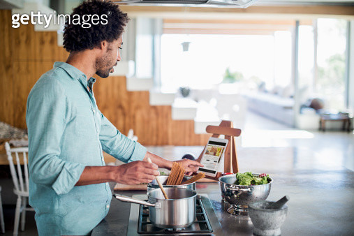 Man cooking in the kitchen while reading a recipe of a digital tablet - gettyimageskorea
