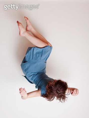 Young woman wearing blue dress falling upside down - gettyimageskorea