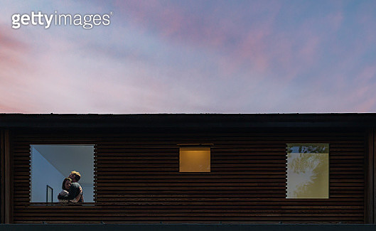 Couple embracing in window at dusk - gettyimageskorea