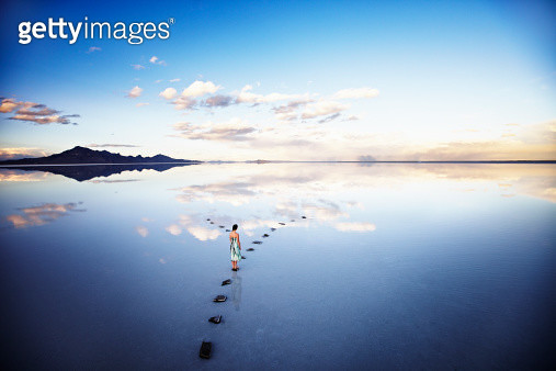 Woman at fork in stone pathway in lake at sunset - gettyimageskorea