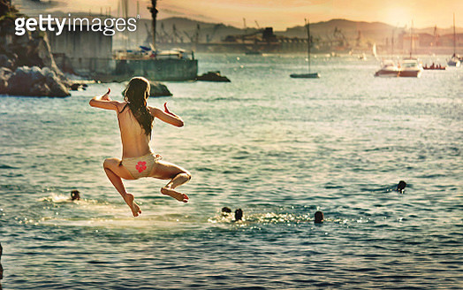 Happiness. Girl jumping into the sea at sunset - gettyimageskorea
