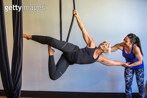 Instructor assisting yoga student hanging from silks - gettyimageskorea