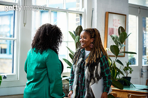 Two women talking in creative office - gettyimageskorea
