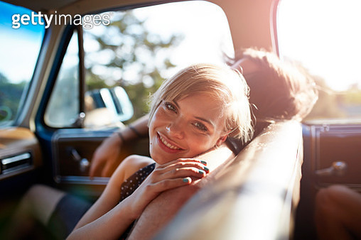 Portrait of cute woman in car, at sunset - gettyimageskorea