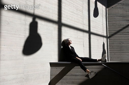 Businesswoman wearing elegant suit sitting on retaining wall with sunlight and shadow in background - gettyimageskorea