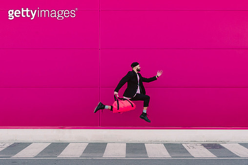 Young man jumping with travelling bag in front of a pink wall - gettyimageskorea