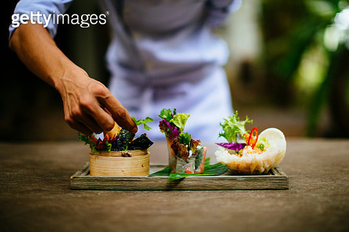 Close up of chef putting the final touches on a dish of salads and spring rolls. - gettyimageskorea