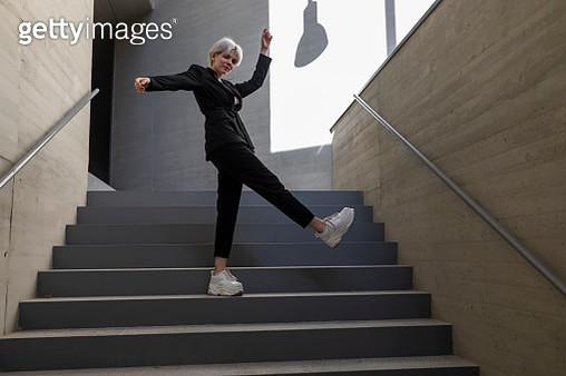 Businesswoman wearing elegant suit dancing on steps in building - gettyimageskorea