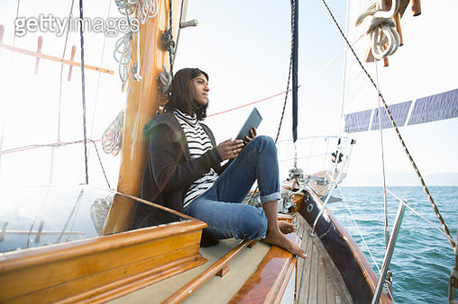 Pensive woman using digital tablet on sailboat - gettyimageskorea