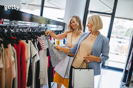 Fashionable senior friends shopping for clothes in urban boutique - gettyimageskorea
