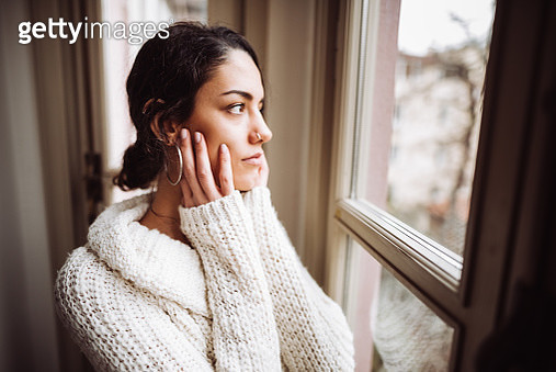 pensive woman in front of the window - gettyimageskorea
