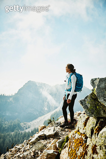 Young woman enjoying view from outlook during hike in mountains - gettyimageskorea