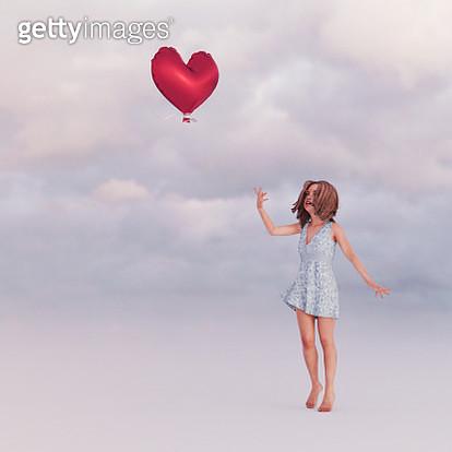Girl releasing heart-shape balloon into sky - gettyimageskorea