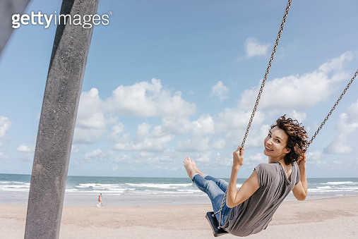 Happy woman on a swing on the beach - gettyimageskorea