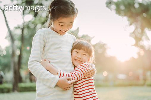 Lovely little sisters hugging & smiling joyfully in park - gettyimageskorea