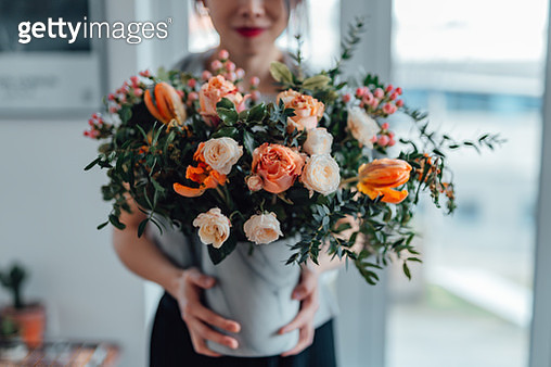 Shot of an unrecognisable woman covering her face with flowers in living room - gettyimageskorea