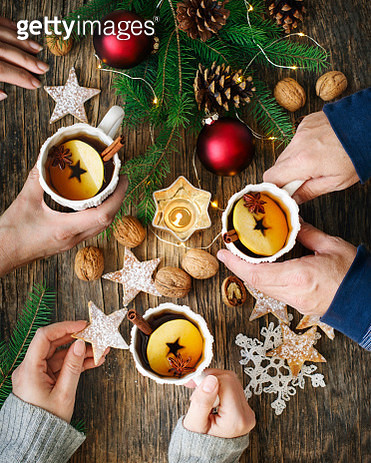 Spiced apple tea. Man and two women drinking tea. Concept of winter holiday - gettyimageskorea